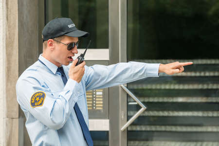 talkie: Young Male Security Guard Gesturing While Using Walkie-talkie