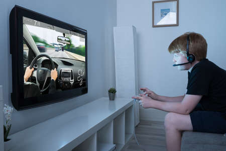 kids playing video games: Boy With Joystick Playing Car Game On Television At Home