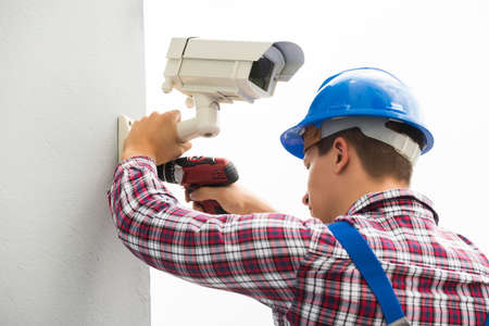 setup man: Young Male Technician Installing Camera On Wall With Screwdriver
