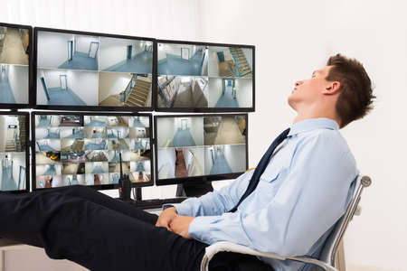 security room: Security Guard Sleeping In Front Of Multiple Computers Showing CCTV Footage Stock Photo