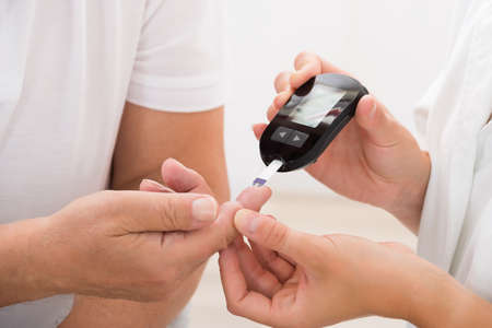 old man on a physical pressure: Close-up Of Doctors Hand Using Glucometer On Patients Finger Stock Photo