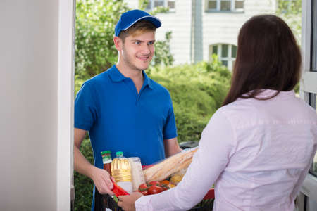 receiving: Woman Receives Groceries From The Delivery Man At Home Stock Photo