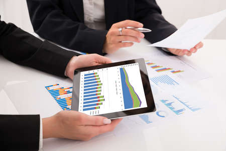 comparing: Close-up Of Businesspeople Comparing Graphs On Digital Tablet In Office