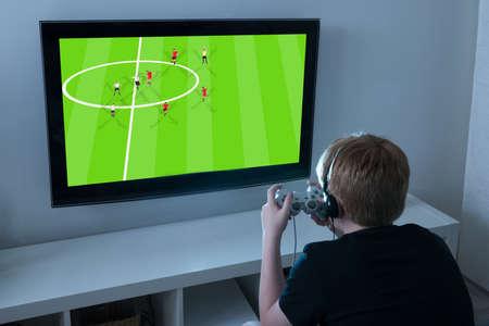 niños jugando videojuegos: Boy con el joystick de videojuegos que juegan al fútbol en la televisión en el hogar