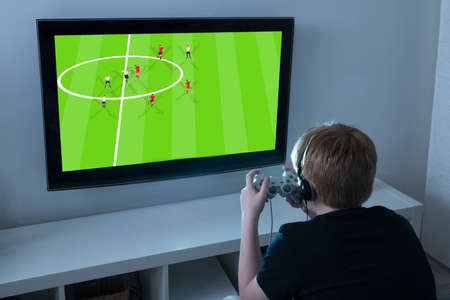 kids playing video games: Boy With Joystick Playing Football Videogame On Television At Home