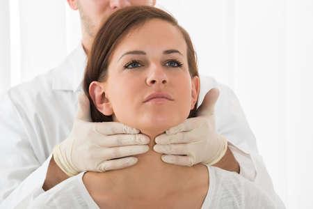 Un doctor Performing palpación Examen físico de la glándula tiroides
