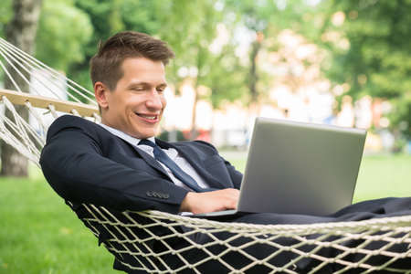 people relax: Happy Young Man Lying In Hammock Using Laptop