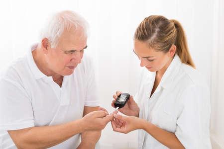 pacientes: Jóvenes mujeres médico Usando glucómetro en el dedo Senior paciente masculino