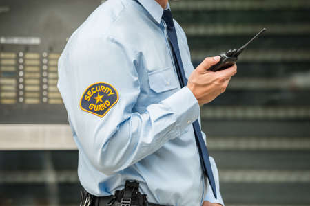 Close-up Photo Of Security Guard Using Walkie-talkie Stock Photo