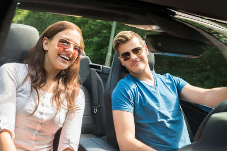 cabrio: Portrait Of Smiling Young Couple In A Car Wearing Sunglasses