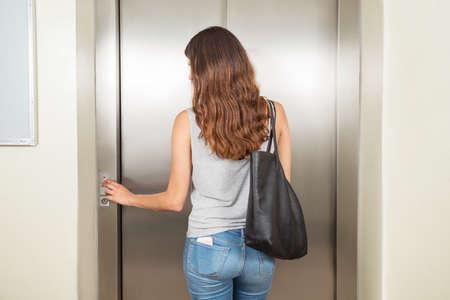 エレベーターを使用してのハンドバッグを持つ若い女性の後姿
