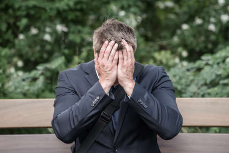 Sad Young Businessman Sitting On Bench Suffering From Headache Stock Photo