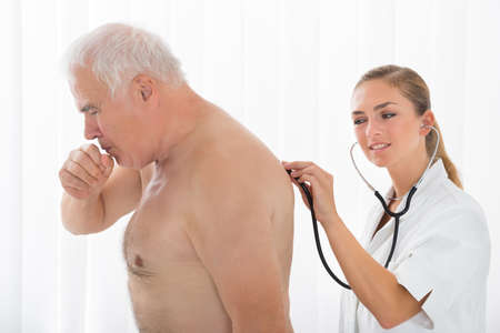 health professional: Young Female Doctor Using Stethoscope On Senior Male Patients Back