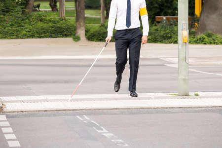 depend: Blind Person With White Stick Walking On Street Stock Photo