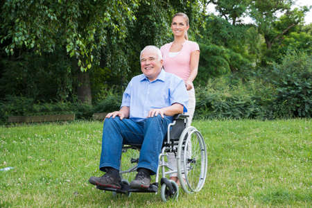 wheelchair access: Smiling Young Woman With Her Disabled Father On Wheelchair In Park