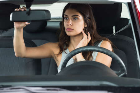 mirror: Young Woman Sitting Inside Car Adjusting Rear View Mirror