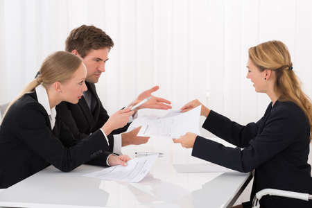 complaining: Unhappy Female Colleague Showing Document To Young Businesspeople In Meeting