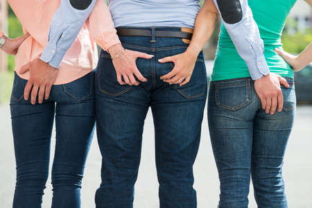 threesome: Rear View Of Friends Holding Each Others Buttock Stock Photo