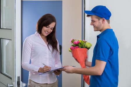 Eine junge Frau, Zeichen für den Eingang der einen Blumenstrauß