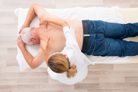 old man on a physical pressure: High Angle View Of A Female Therapist Giving Massage To Senior Man In Spa