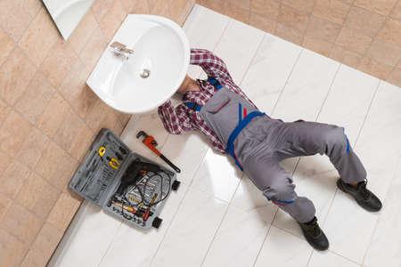 High Angle View Of Male Plumber Lying On Floor Repairing Sink In Bathroom