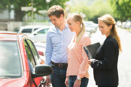 sell car: Saleswoman Standing Besides Couple Looking At New Red Car