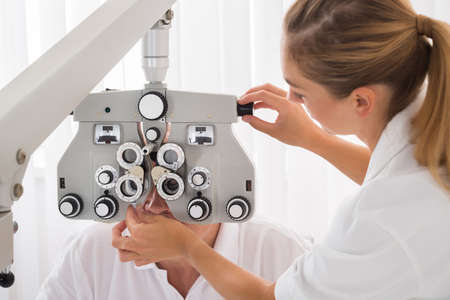 two visions: Happy Female Optometrist Doing Sight Testing For Patient In Clinic