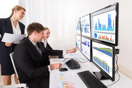 Happy Businesspeople Analyse Jeunes graphiques sur plusieurs ordinateurs Dans Office Banque d'images - 62331646