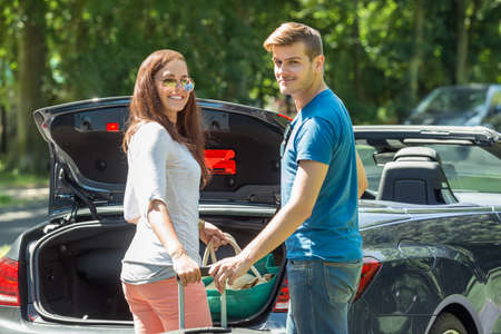 going: Portrait Of Young Happy Couple Putting Luggage In A Car Trunk Stock Photo