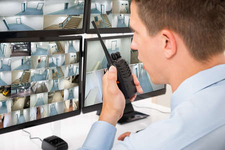 talkie: Close-up Of Male Security Guard Talking On Walkie-talkie While Monitoring Multiple CCTV Footage