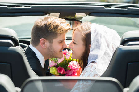 casados: Newlyweds Young Smiling Couple Kissing In The Wedding Car