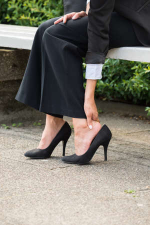 unfit: Close-up Of Businesswomans Hand Sitting On Bench Removing High Heels Stock Photo