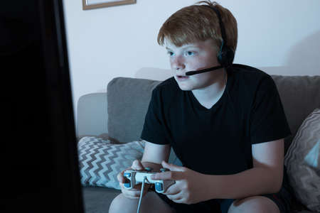 Boy With Joystick Engrossed In Playing Videogames At Home