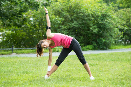 Young Woman Listening To Music On Headphone While Exercising In Park