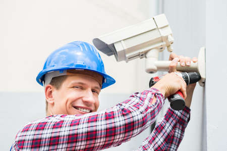 setup man: Close-up Of Happy Male Technician Installing Camera On Wall Stock Photo