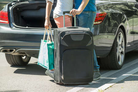 Close-up Of Couple Putting Luggage In A Car Trunk