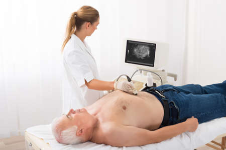 diagnose: Young Female Doctor Using Ultrasound Scan On Abdomen Of Senior Male Patient In Clinic Stock Photo