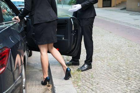 Chofer Hombre de abrir la puerta del coche para La Empresaria En la calle Foto de archivo