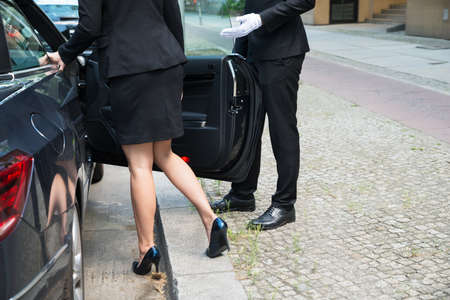 chofer: Chofer Hombre de abrir la puerta del coche para La Empresaria En la calle Foto de archivo