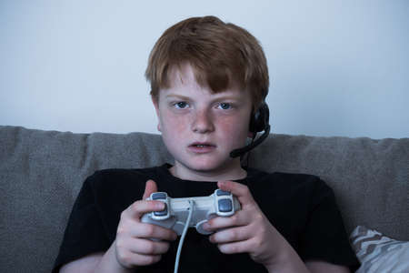 kids playing video games: Portrait Of Boy With A Joystick Playing Videogames At Home