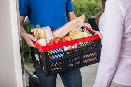 Close-up Of Man Delivers Crate Of Groceries At Home Stockfoto