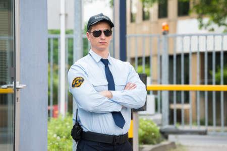 Überzeugter junger Mann Security Guard Standing Arm verschränkt