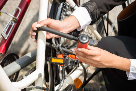 locking up: Close-up Of Businesswomans Hand Locking Up Her Bicycle Stock Photo