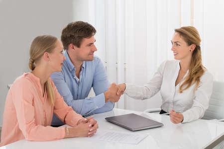 女性コンサルタントのデスクに、幸せな若いカップルと握手 写真素材