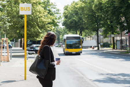 Jeune femme d'affaires avec élimination de la Coupe Waiting For Bus