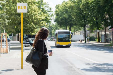 Młoda Businesswoman Z Kubek Do Zużycia Oczekiwanie Na Autobus