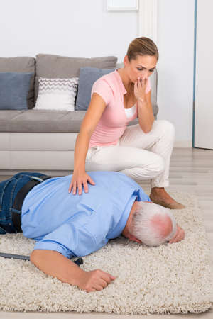 fainted: Shocked Young Woman Looking At Her Fainted Disabled Father Lying On Carpet