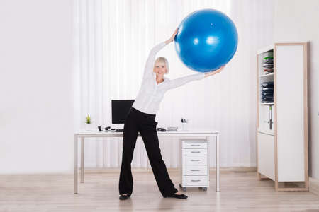 ball stretching: Happy Businesswoman Stretching Her Arms Using Fitness Ball In Office