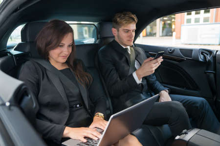 seatbelt: Portrait Of Young Businessman With Smart Phone And Businesswoman Using Laptop In The Car