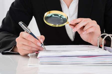 Close-up Der Auditor Inspecting Finanzdokumente am Schreibtisch
